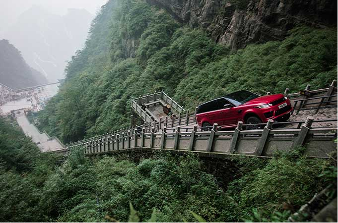 A red Land Rover Sport climbing a portion of the 999 steps