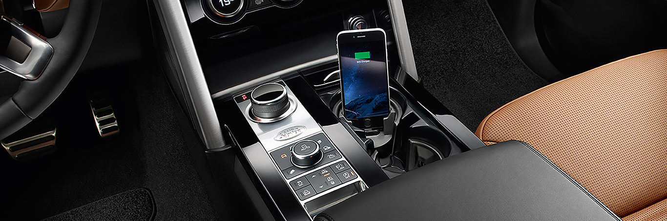 iPod charging dock in the cupholder of a Land Rover, chestnut brown interior